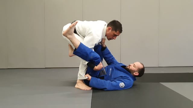 Attaque en knee slide et stack pass pour faire réagir l'adversaire qui a une saisie forte au pantalon en de la Riva