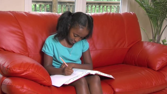 Girl Sits on a Couch Doing Homework