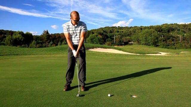 Golfer Putting a Golf Ball into a Hole