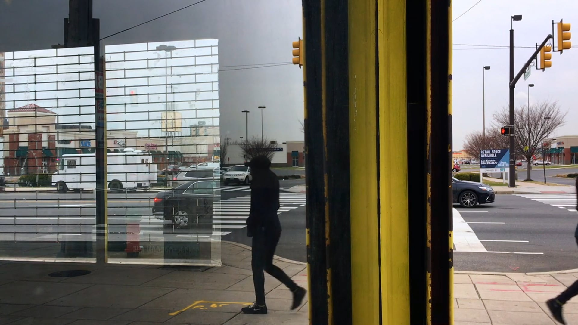 Chiasmus, 2018, 5:16 min digital video  Daily life is documented and visually collapsed through the reflective windows of a vacant commercial storefront in Philadelphia. The city intersection is reflected in the window pictured and through the store's security roll gate. The intersection is flanked by strip malls in South Philadelphia, an urban area experiencing gentrification. The landscape of the city is visually confused alongside a sense of the neighborhood's rapid economic shift.