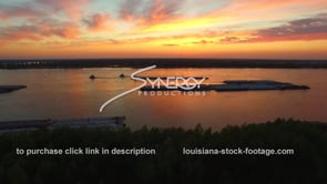 187 treeline aerial reveal of epic stunning sunset with barges on mississippi river aerial