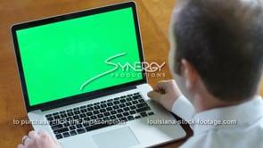 1850 Millennial business man watches video laptop green screen