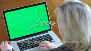 1852 Lady watches video on laptop green screen